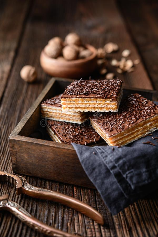 Homemade sweet wafer filled with walnut toffee filling and topped with chocolate frosting. On wooden background royalty free stock photography