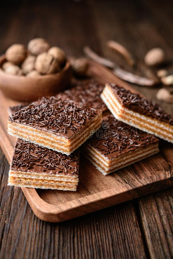 Homemade sweet wafer filled with walnut toffee filling and topped with chocolate frosting. On wooden background royalty free stock images