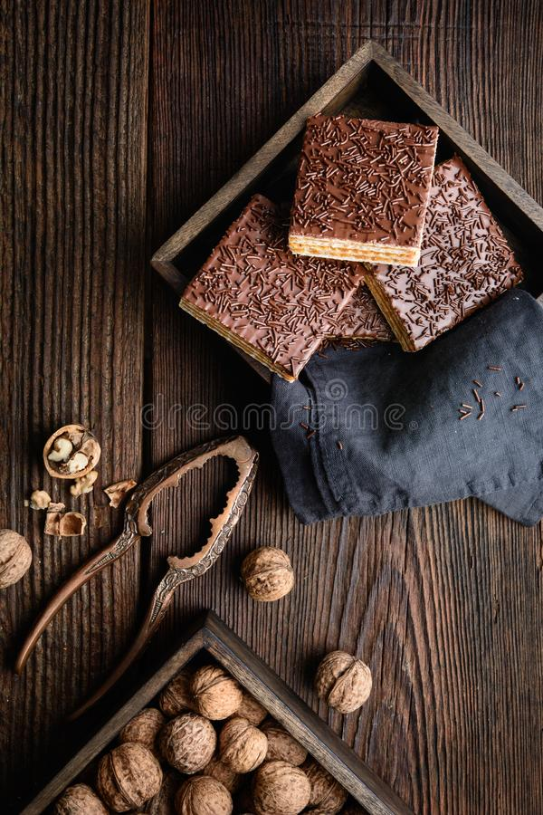 Homemade sweet wafer filled with walnut toffee filling and topped with chocolate frosting. On wooden background royalty free stock image