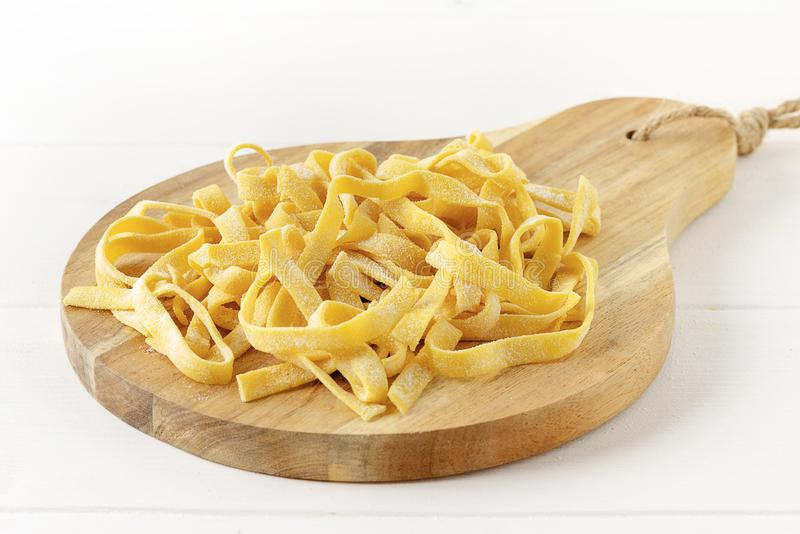 Homemade tagliatelle on chopping board on wooden white background. Homemade tagliatelle on chopping board stock photo