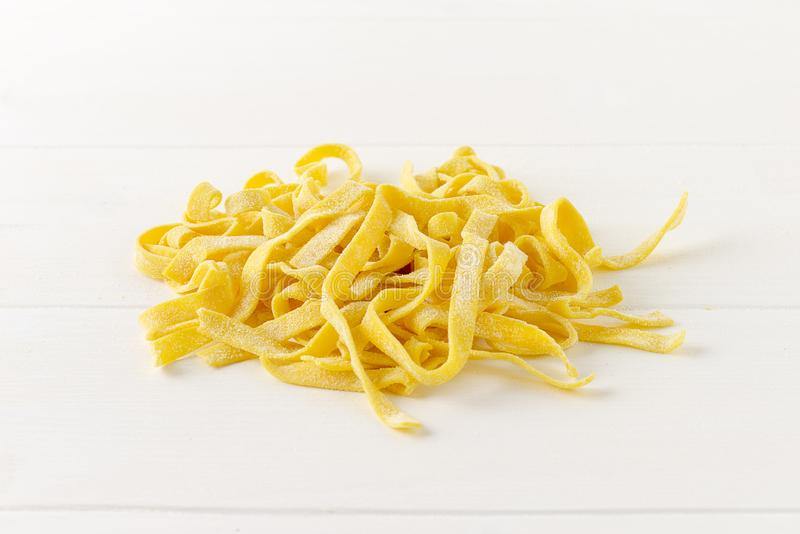 Homemade tagliatelle on wooden white background royalty free stock image