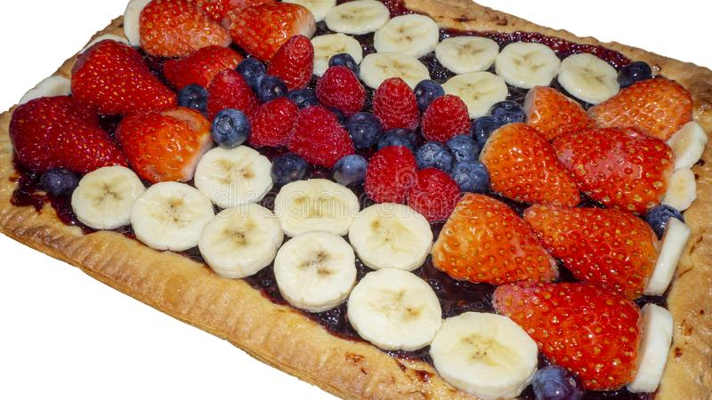 Homemade tart with fresh fruit, strawberries, bananas, blueberries and raspberries royalty free stock photography