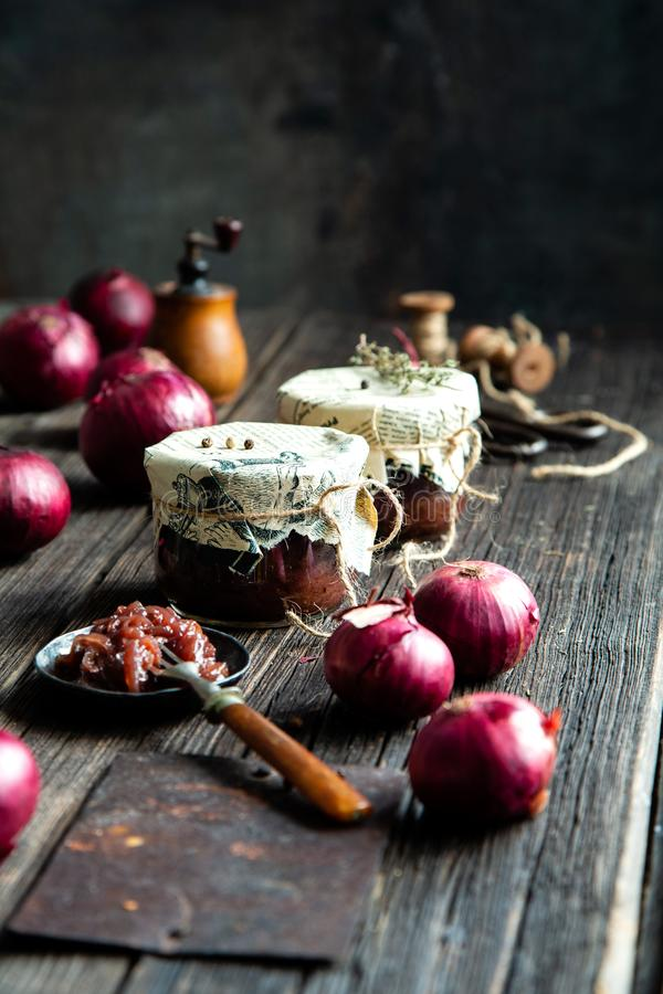 Homemade tasty canned onion red jam, marmalade, confiture, chutney in two glass jars on rustic wooden table stock photography