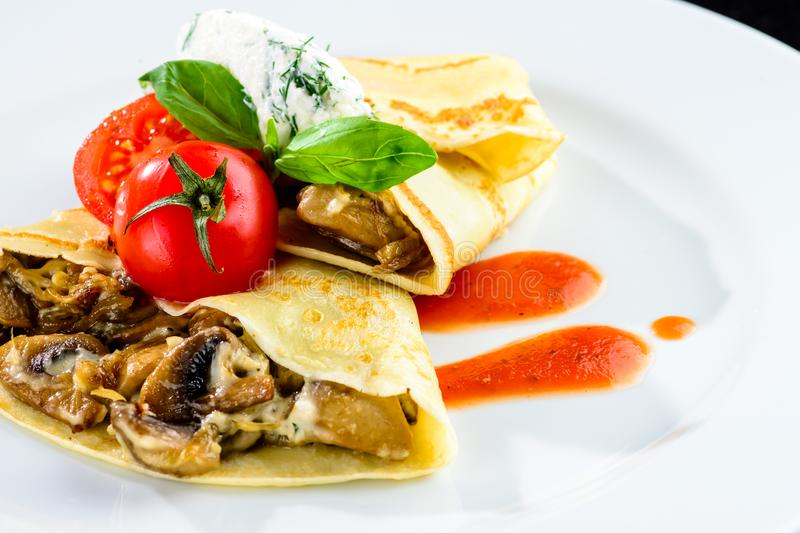 Homemade tasty pancakes blinis served with mushrooms and tomat stock photos