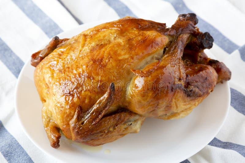 Homemade tasty rotisserie chicken on white plate, side view. Close-up. Homemade tasty rotisserie chicken on white plate, side view royalty free stock photo
