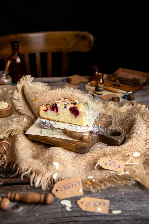Homemade tasty slice of biscuit cake with cherries, almond flakes, powdered sugar on top. On wooden board on rustic wooden table with sackcloth, bottles, forks stock photography