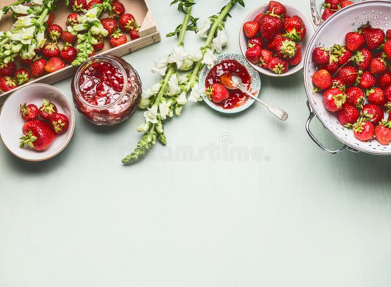 Homemade tasty strawberries jam in glass jar with summer flowers and fresh berries, bowls and spoon on table background, top view. royalty free stock image