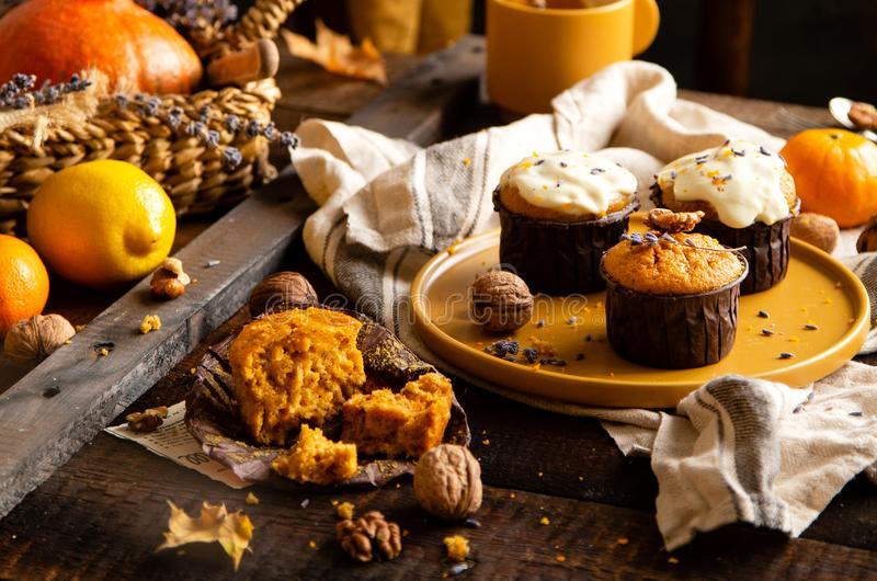Homemade tasty sweet orange pumpkin muffins or cupcakes with white cream, lavender, zest, nuts royalty free stock images