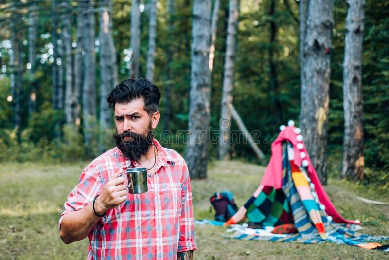 Homemade tent - hut. Handsome bearded man having fun in adventure Park. stock photos