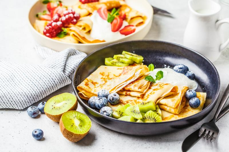 Homemade thin crepes served with curd cream, fruits and berries in black and white plates royalty free stock image