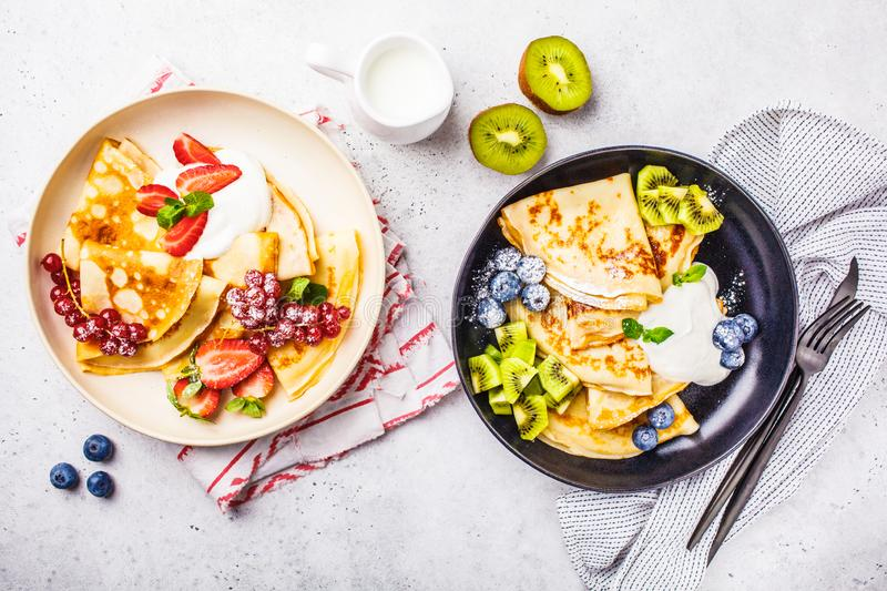 Homemade thin crepes served with curd cream, fruits and berries in black and white plates, top view. Homemade thin crepes served with curd cream, fruits and stock images