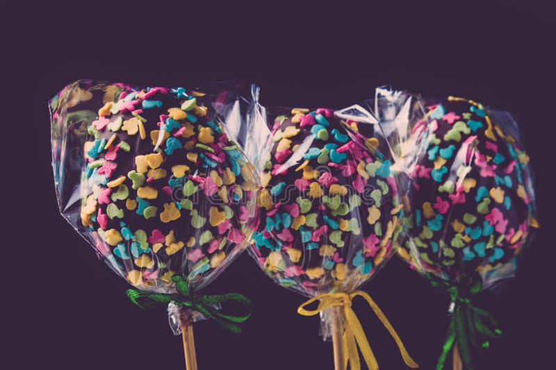 Homemade tiny cakes - cake pops in egg shape on a dark background. Easter theme. Toned stock image