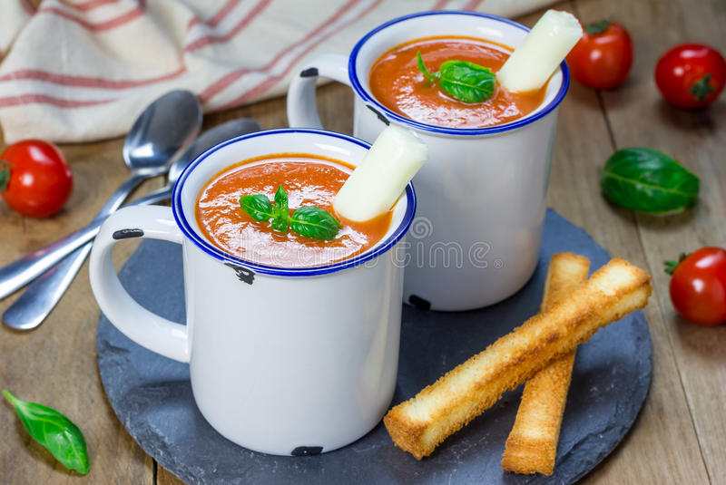 Homemade tomato basil soup in the mug, served with mozzarella cheese stick. And croutons stock photos