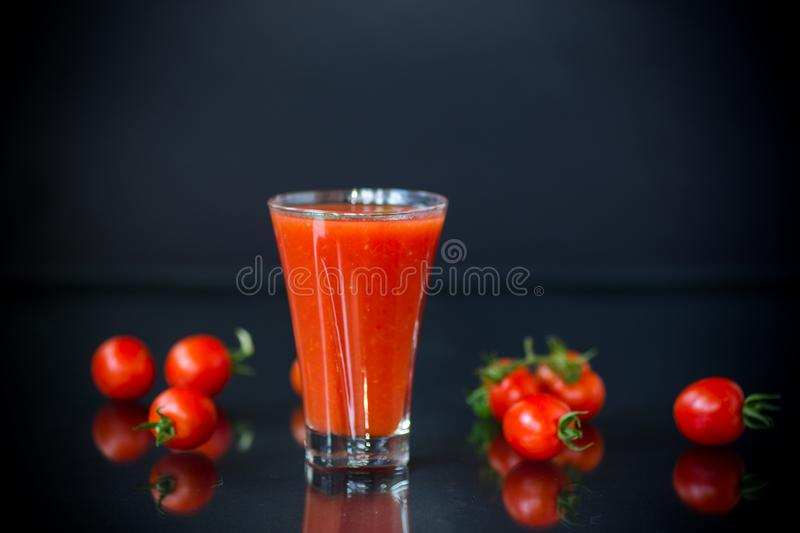 Homemade tomato juice in a glass and fresh tomatoes royalty free stock images