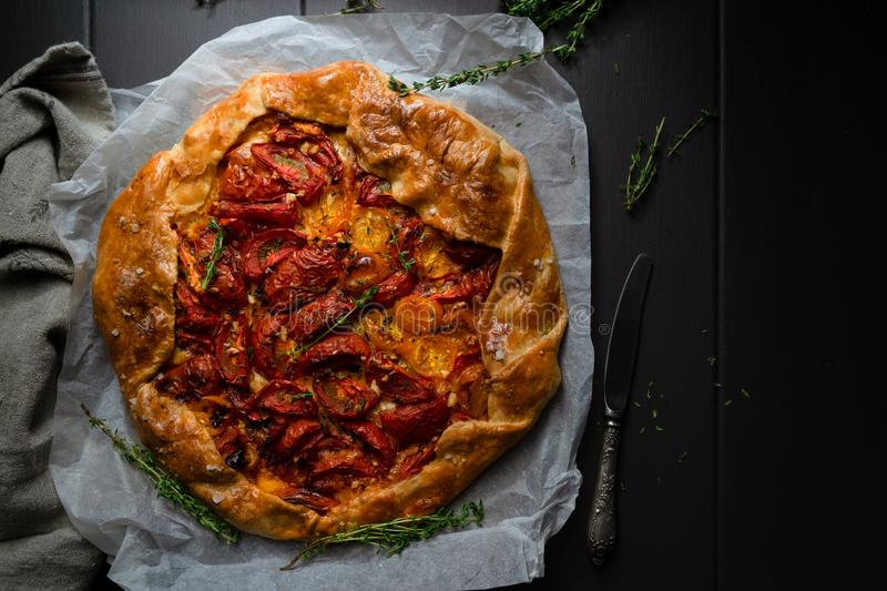 Homemade tomato and thyme tart, low key image. Horizontal orientation with copy space stock images