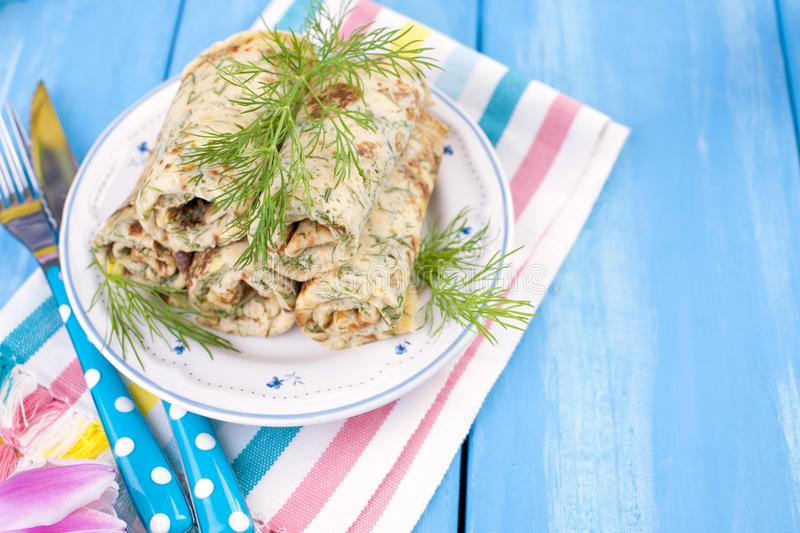 Homemade traditional pancakes with dill for spring carnival. Russian breakfast. Bright flowers of tulips. Blue background. A free royalty free stock image