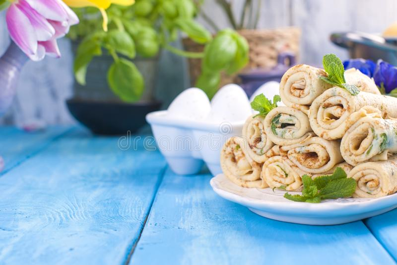 Homemade traditional pancakes with dill for spring carnival. Russian breakfast. Bright flowers of tulips. Blue background. A free royalty free stock photography