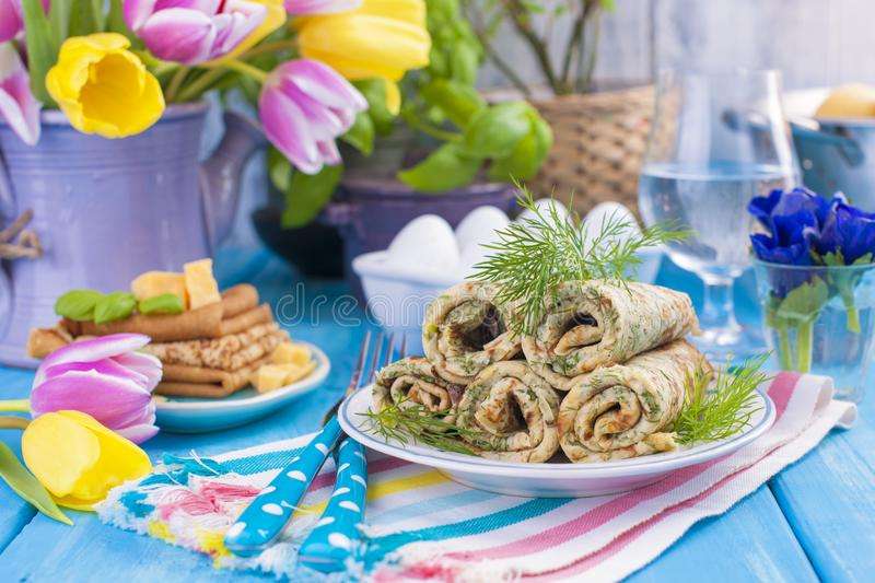 Homemade traditional pancakes with dill for spring carnival. Russian breakfast. Bright flowers of tulips. Blue background. A free royalty free stock photos