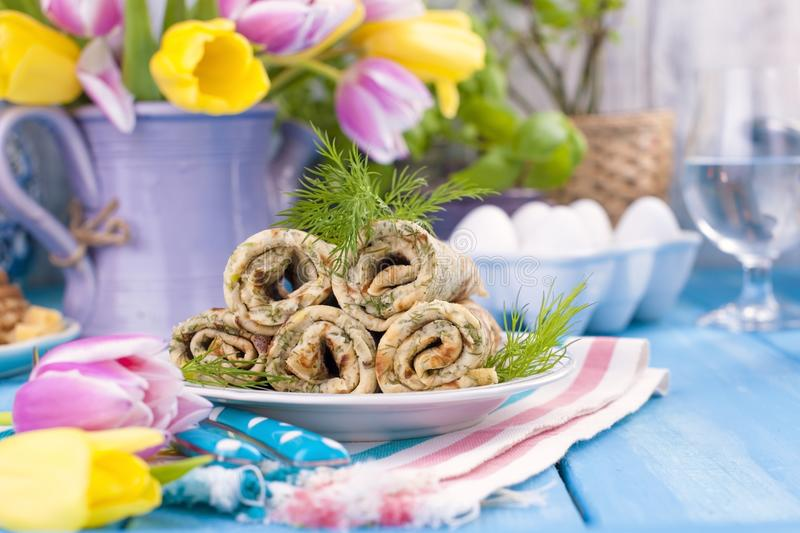Homemade traditional pancakes with dill for spring carnival. Russian breakfast. Bright flowers of tulips. Blue background. A free stock photography