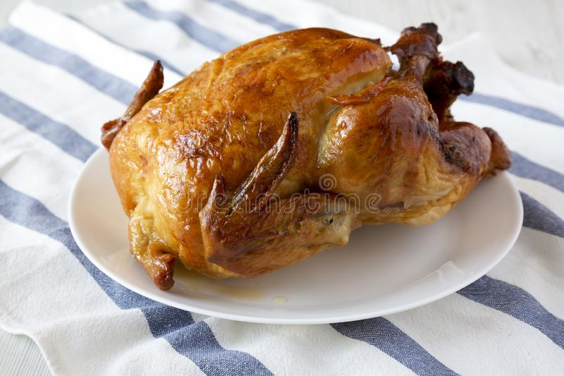 Homemade rotisserie chicken on white plate, side view. Close-up royalty free stock images