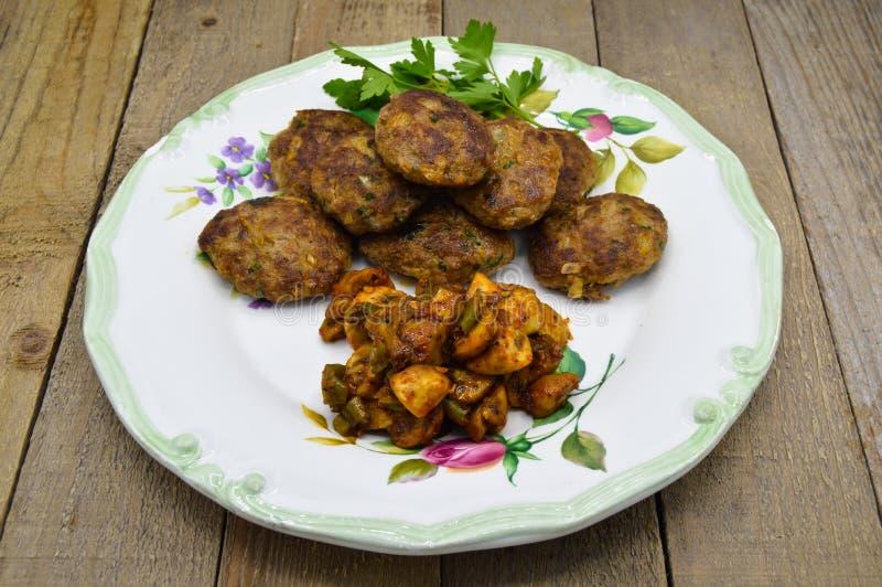 Homemade Turkish meatballs kofte or kofta and saute the mushrooms royalty free stock images