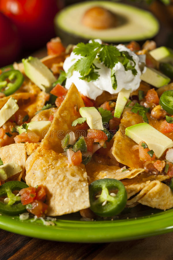 Homemade Unhealthy Nachos with Cheese and Vegetables royalty free stock photos