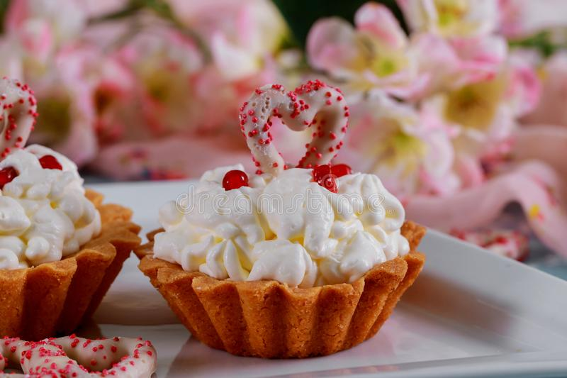 Homemade valentine cupcakes with red sugar hearts and pink flowers background stock photography