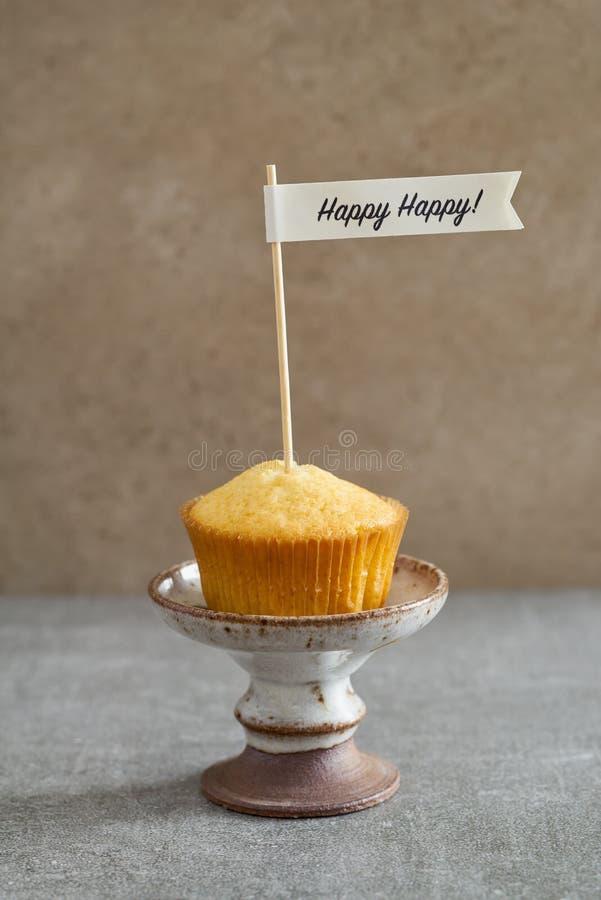 Homemade vanilla birthday cupcake. Homemade vanilla cupcake with a handcrafted birthday cake pick on rustic mini cake stand stock image