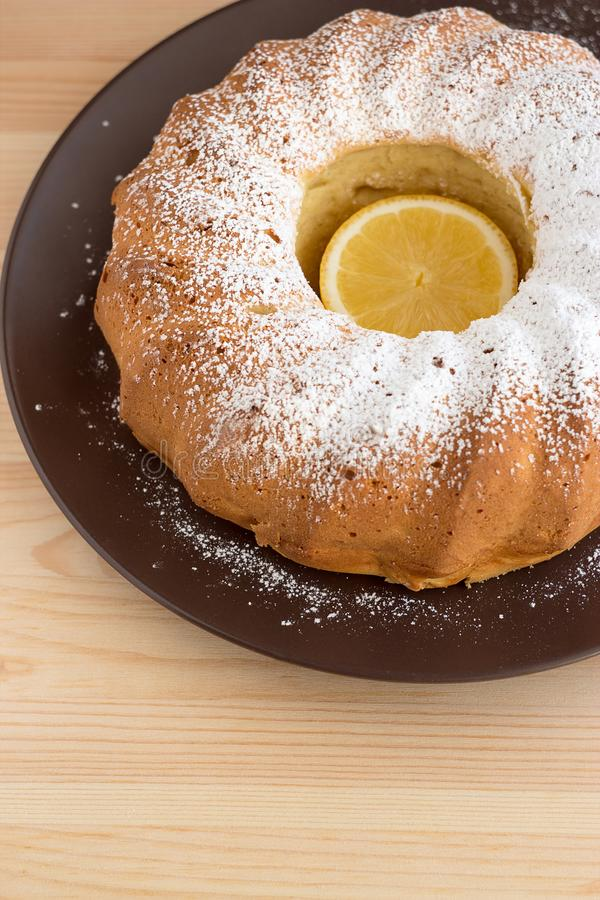 Homemade vanilla bundt cake with lemon, sprinkled with powdered sugar icing on a brown plate on a wooden background. stock photography