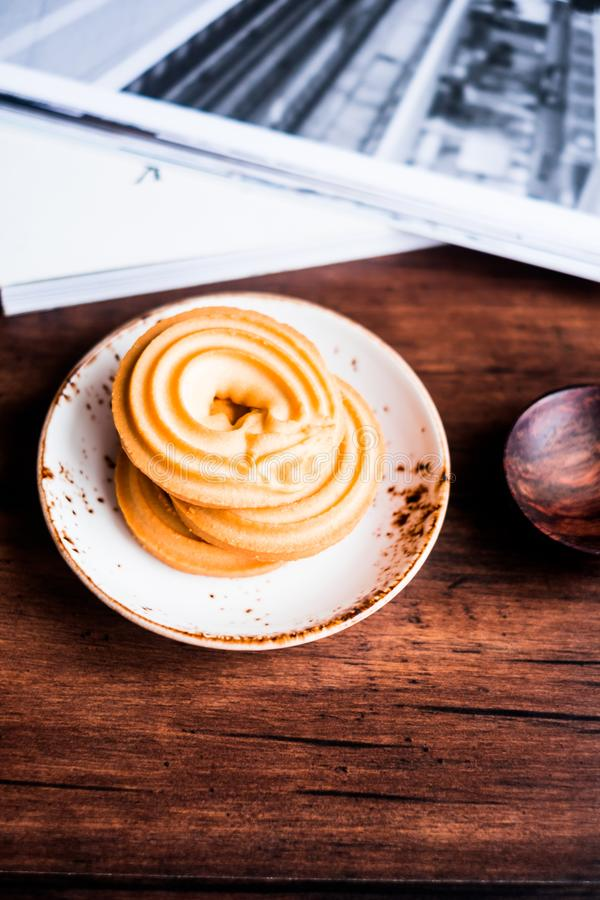 Homemade vanilla butter cookies in the shape of rings stacked on a dessert plate on a wooden table, selective focus. Image with co stock photo