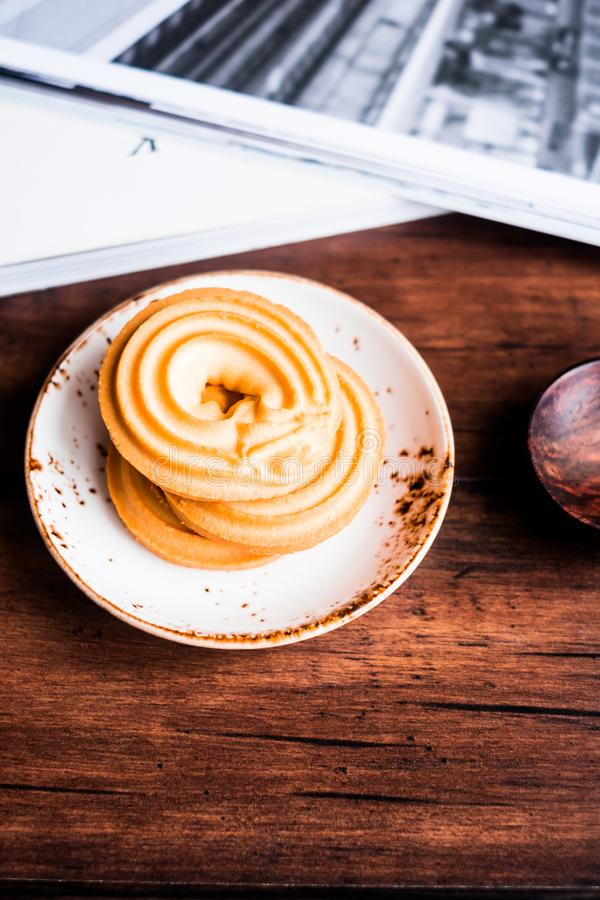 Homemade vanilla butter cookies in the shape of rings stacked on a dessert plate on a wooden table, selective focus. Image with co royalty free stock image