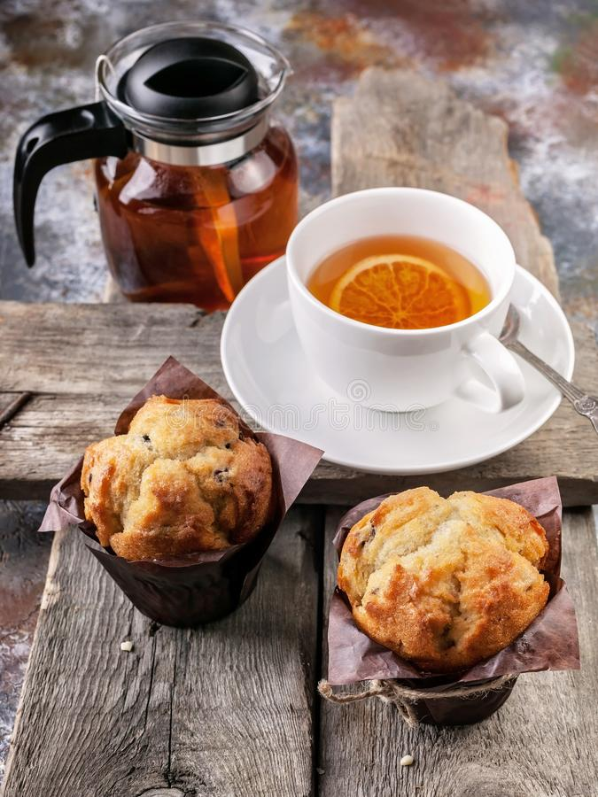 Homemade vanilla Muffins and flavored tea on a rustic wooden background. Close-up. Vertical shot royalty free stock photos