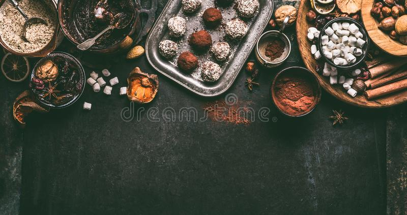 Homemade vegan chocolate truffle pralines with dried fruits and nuts mix ingredients on dark background, top view, border. Healthy sweets. Energy vegan balls royalty free stock images