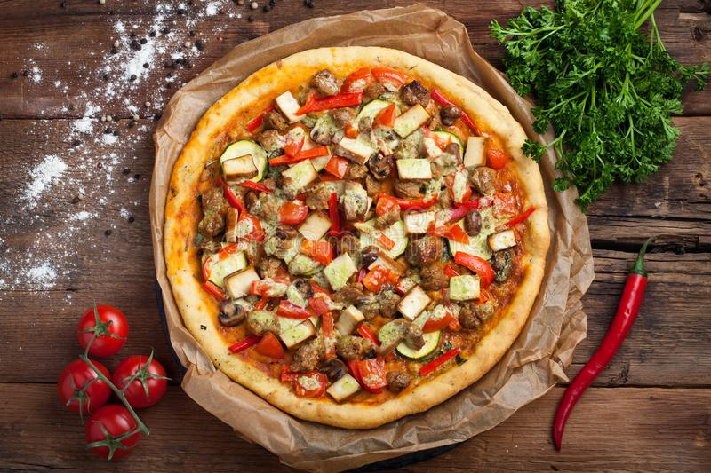 Homemade vegan pizza with tomatoes, zucchini, bell peppers, mushrooms and soy meat on an old wooden table. Top view stock image