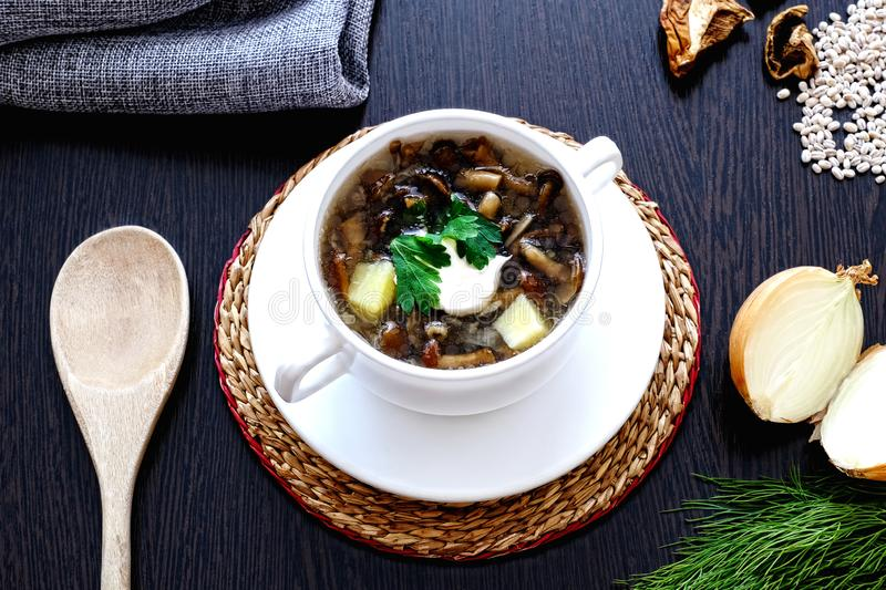 Homemade vegetarian mushroom soup with pearl barley and vegetables in a white Cup with two handles royalty free stock image