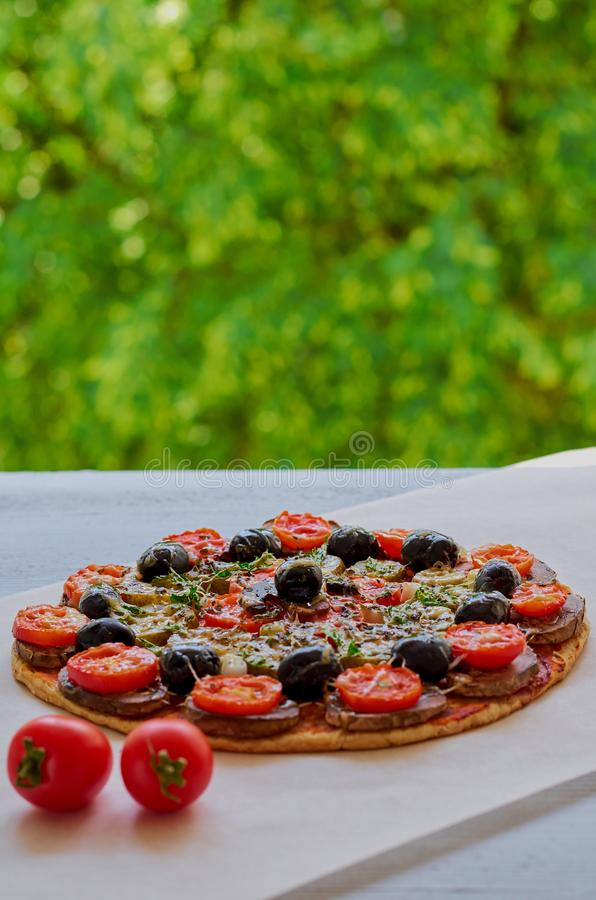Homemade veggie pizza with mushrooms, black olives and herbs on the gray kitchen table decorated with fresh cherry tomatoes stock photography