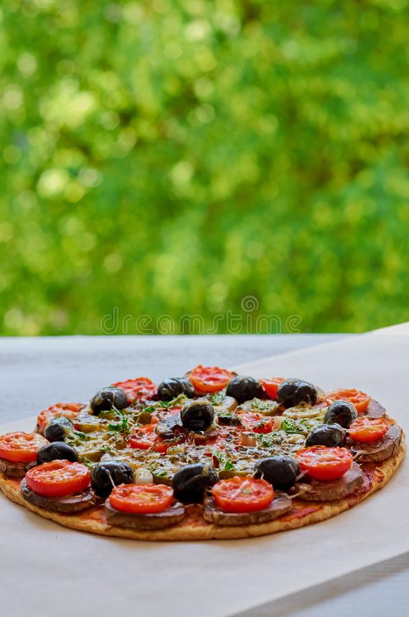 Homemade veggie pizza with mushrooms, cherry tomatoes, black olives and herbs on the kitchen table Pizza on the blurred background stock photos