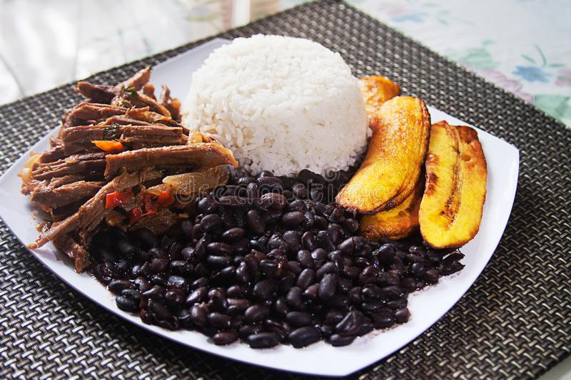 Homemade Venezuelan food. Traditional Venezuelan dish. Pabellon Criollo. White Rice, Black beans,Fried plantains, and Shredded beef royalty free stock photos