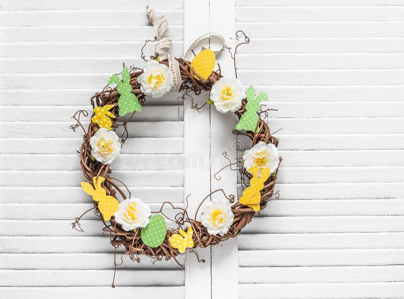 Homemade vine easter wreath with flowers and paper bunnies on a light background. Easter decoration for the house. Creativity. Concept royalty free stock photo
