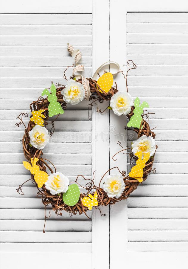 Homemade vine easter wreath with flowers and paper bunnies on a light background. Easter decoration for the house. Creativity. Concept stock photos