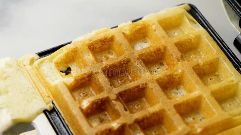 A homemade waffle finished baking on a waffle iron stock photo