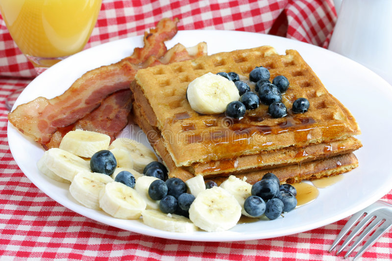 Homemade waffles, bacon, and fruit stock photo