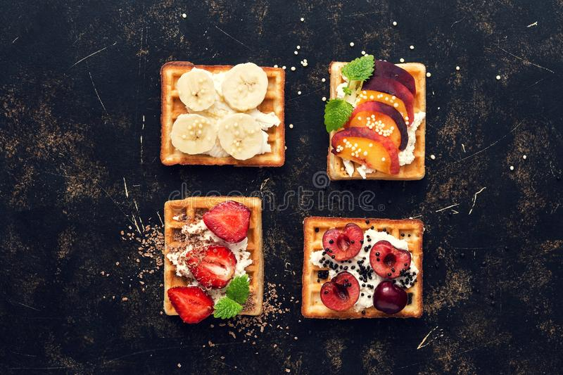 Homemade waffles with berries and fruit on a dark rustic background. Waffles with a variety of filling-banana, cherry, peach, stra stock photos