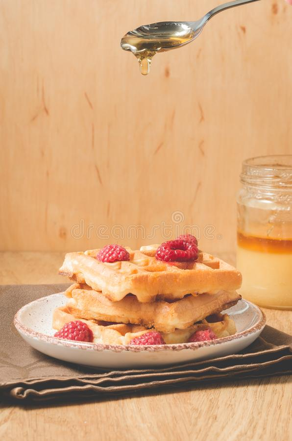 Homemade waffles with berries in plate poured by honey from a spoon/Homemade waffles with berries in plate poured by honey from a. Spoon on a old wooden royalty free stock photography