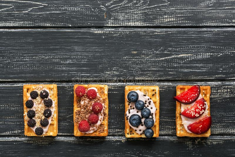 Homemade waffles with blueberries, raspberries and peaches on a black wooden rustic background. Belgian traditional waffle. Flat l royalty free stock images