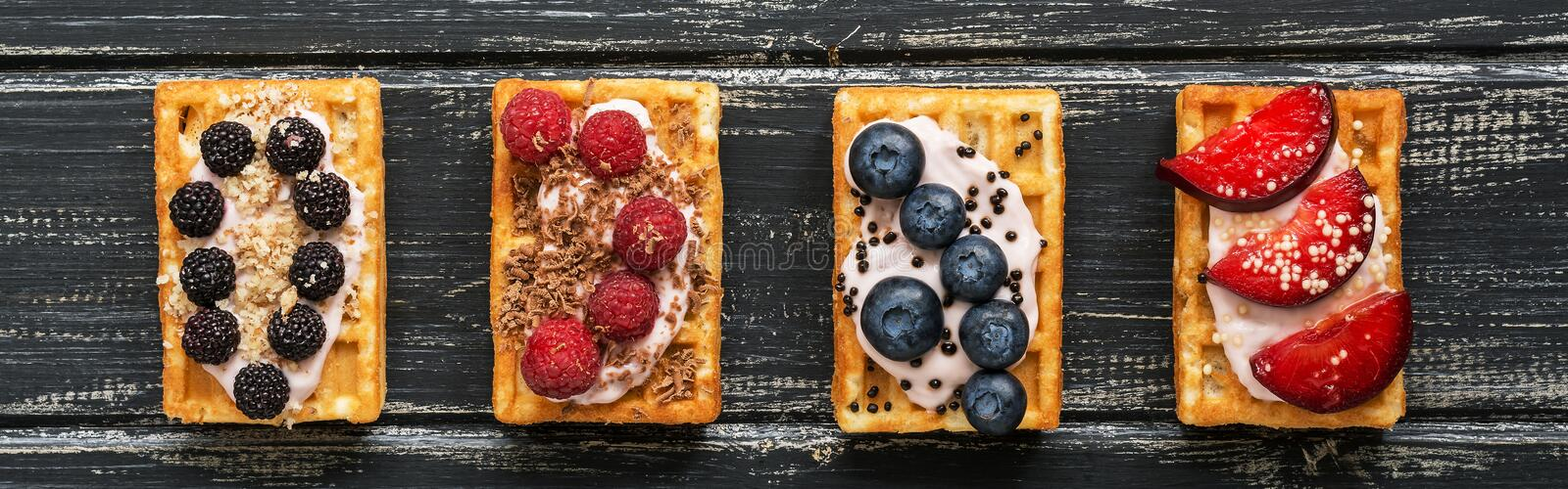 Homemade waffles with blueberries, raspberries and peaches on a black wooden rustic background,border. Belgian traditional waffle stock photos