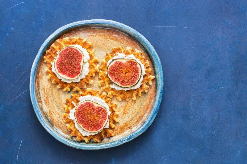 Homemade waffles with cream and figs in a plate on a blue background. Top view, copy space,flat lay. stock photography