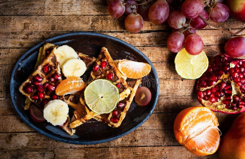 Homemade waffles served with various fruits stock image