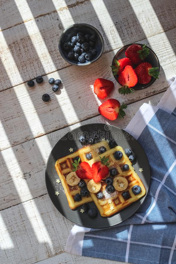 Homemade waffles with strawberries and blueberries for summer breakfast under the striped shadow stock photos