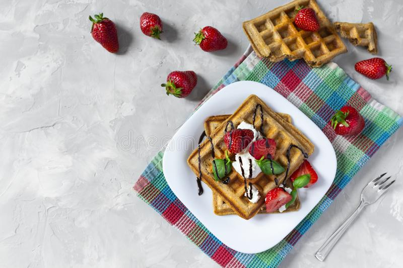 Homemade waffles with strawberries, ricotta cheese and chocolate on white plate. Flat lay, copy space. Homemade square Belgian waffles with strawberries, ricotta royalty free stock photography